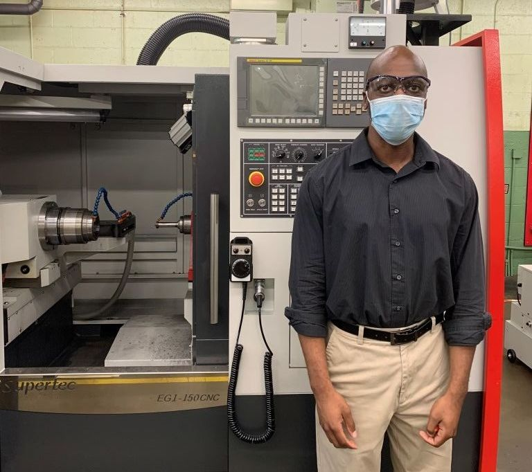 Melvin stood next to one of the new CNC grinding machines at H&T Waterbury.
